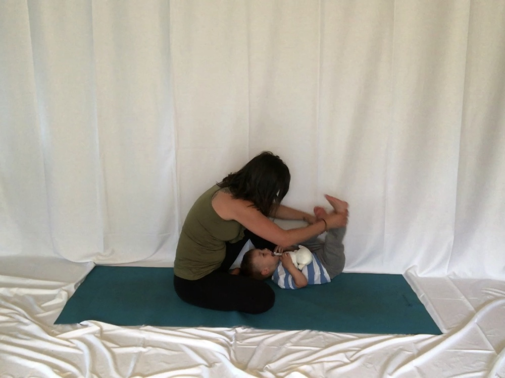 Mama, seated, with her toddler boy who is laying down. His feet are in the air and she is holding on to his ankles.