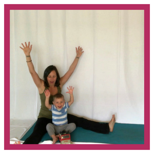 Woman and child on yoga mat with arms in the air.