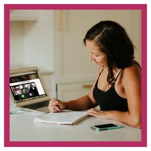 Woman at computer, taking notes.