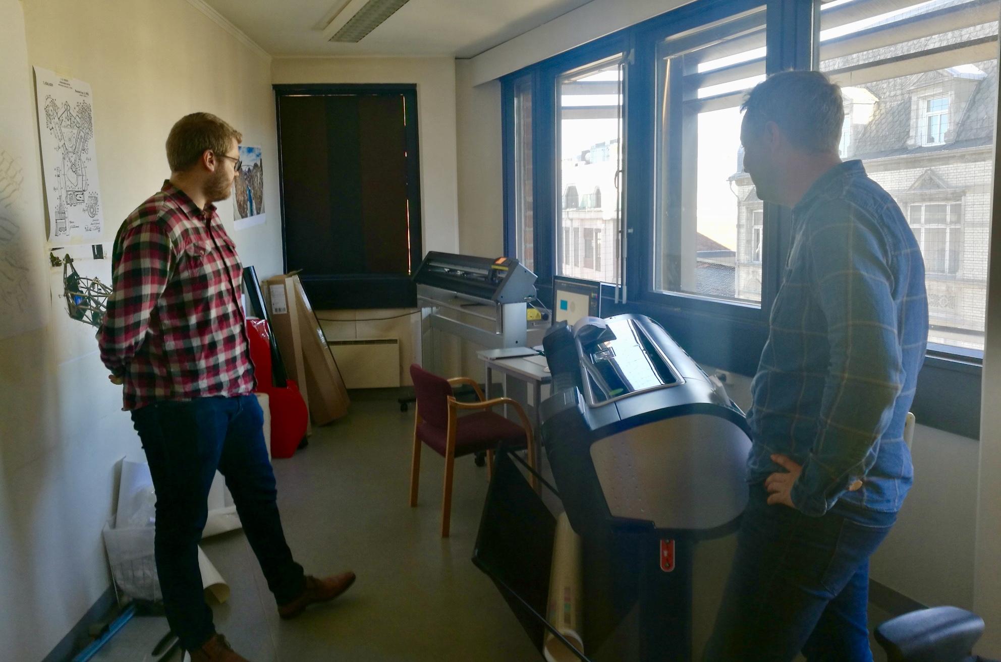 Hjelpende hender:  To studenter fra Nils Sannes andre arbeidsplass på NMBU, Fredrik Vangsal og Fredrik Larsen, er på plass i fjerde etasje hver mandag for å hjelpe elevene med teknologien. – De er ivrige. Hvordan håndtere folieskjæreren hadde de googlet seg frem til på forhånd. Dermed var det ingen vits i å gjennomgå det i timen. Mange av dem kan nok til å kunne jobbe i et trykkeri nå, slår Fredrik Vangsal. (til venstre) fast.