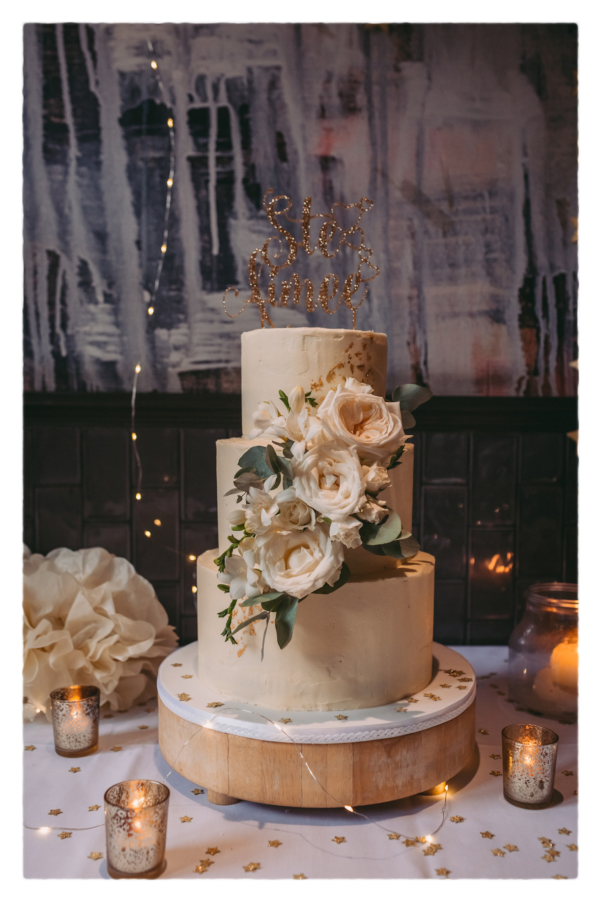 Buttercream wedding cake decorated with gold and fresh flowers