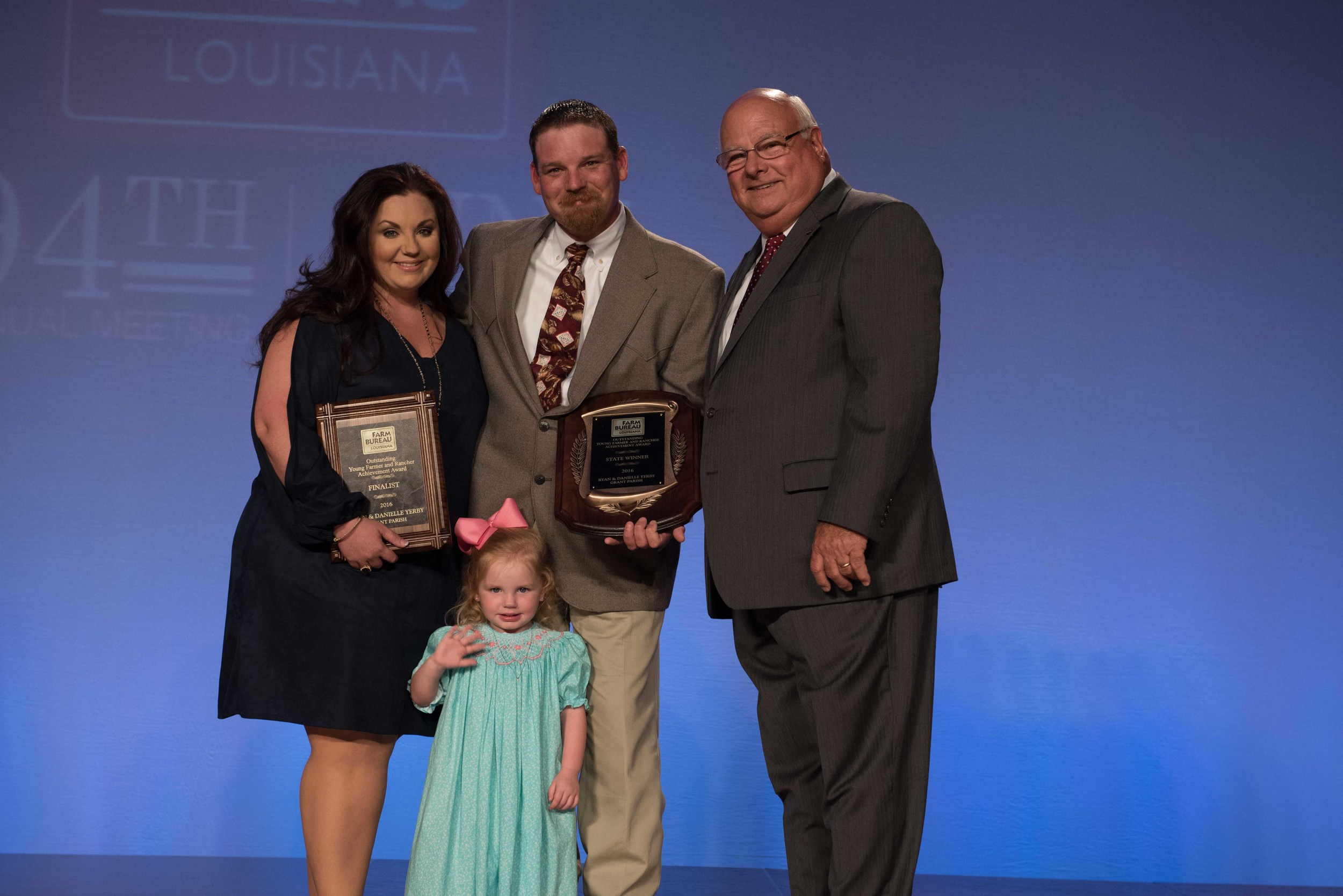Ryan and Danielle Yerby of Grant Parish accept the 2016 Young Farmer and Rancher Achievement Award Thursday, June 23. Pictured, left to right: Danielle Yerby, Ryan Yerby, Reagan Yerby (front) and Louisiana Farm Bureau President Ronnie Anderson.