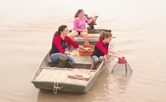 Natachia Stelly baits crawfish traps with two of her daughters on their 2800 acre farm in Vermillion parish.