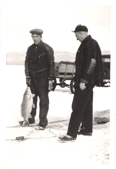 Pictured on the left is O.E. Dosdall, and on the right, the Game Warden oversees the crew to make sure game fish are tossed back into the lake.