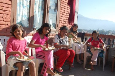 Some of the children and a helper having lunch at the orphanage.
