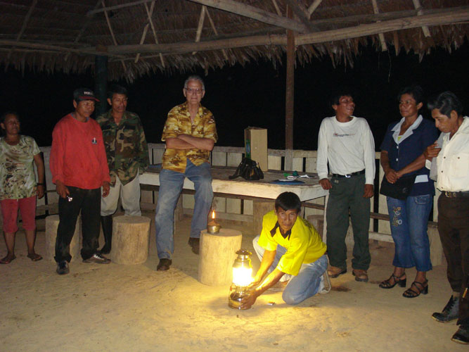 Community villagers gather around kerosene lamp presented by LNDI.