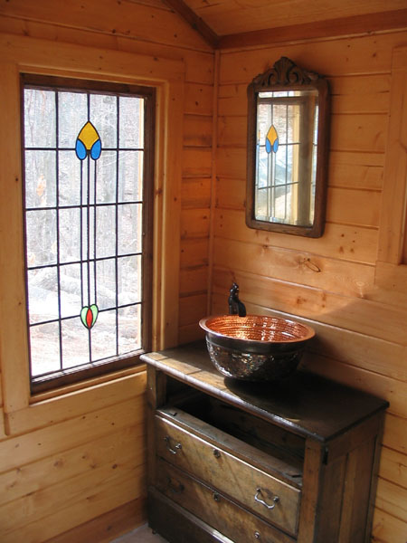 George took an old primitive dresser and made it into a bathroom cabinet. Copper sink and pump handle faucet add a nice touch.
