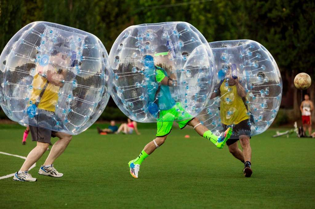 """Players push downfield, often to collide, while encased in bouncy, blue orbs as part of Seattle's first """"Bubble Futbol"""" - or soccer - tournament Sunday, September 7, 2014, at Cal Anderson Park in Capitol Hill in Seattle, Washington. The unlikely sport originated in Europe and is quickly sweeping the U.S., with a recent spotlight on The Tonight Show with Jimmy Fallon.The event was put on by Seattle-local nonprofit """"The World is Fun"""" as a celebration of the organization's fifth anniversary.   Photo: JORDAN STEAD, SEATTLEPI.COM"""