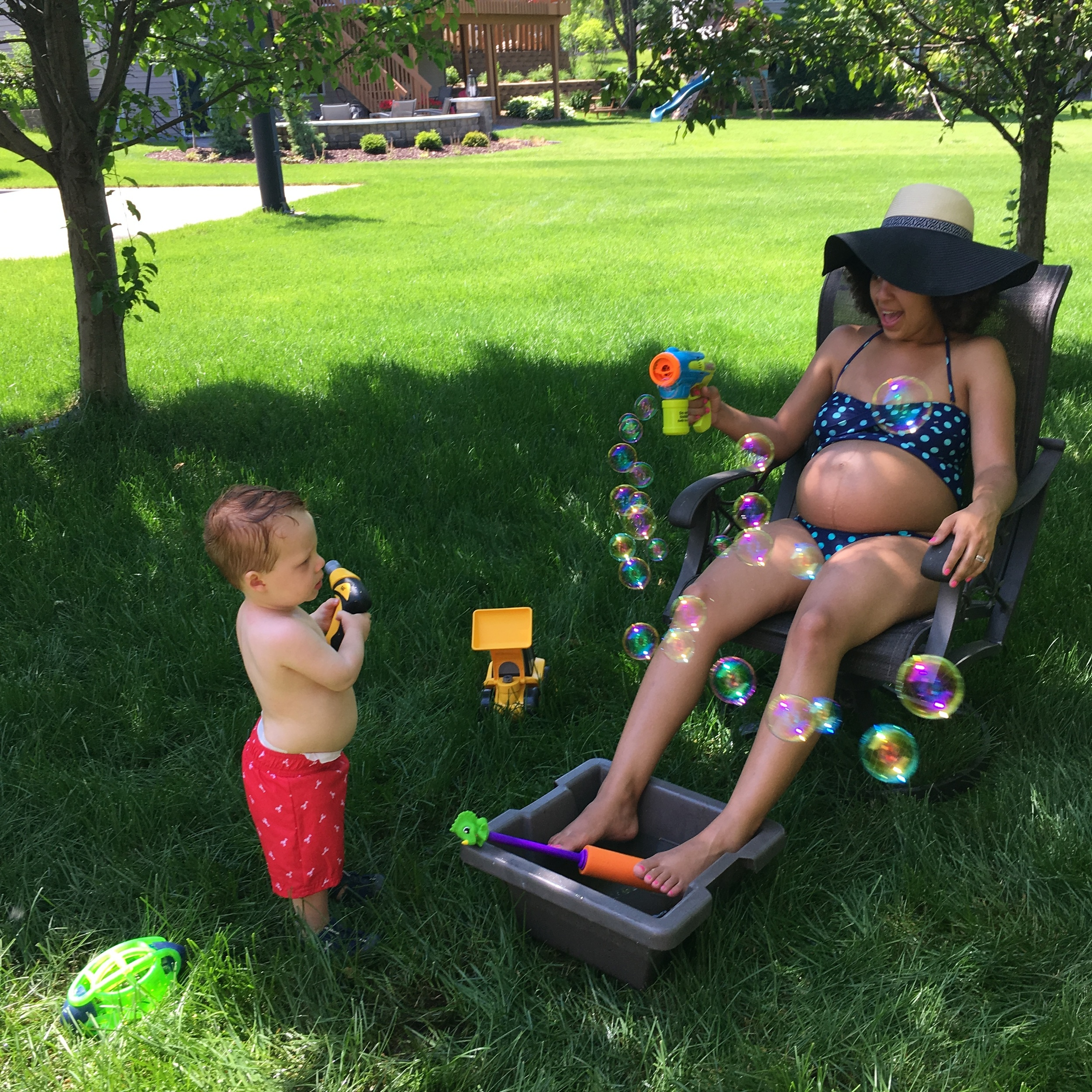 Summer essentials for the eternally pregnant:shade, sunhat, cold water bucket and bubbles.