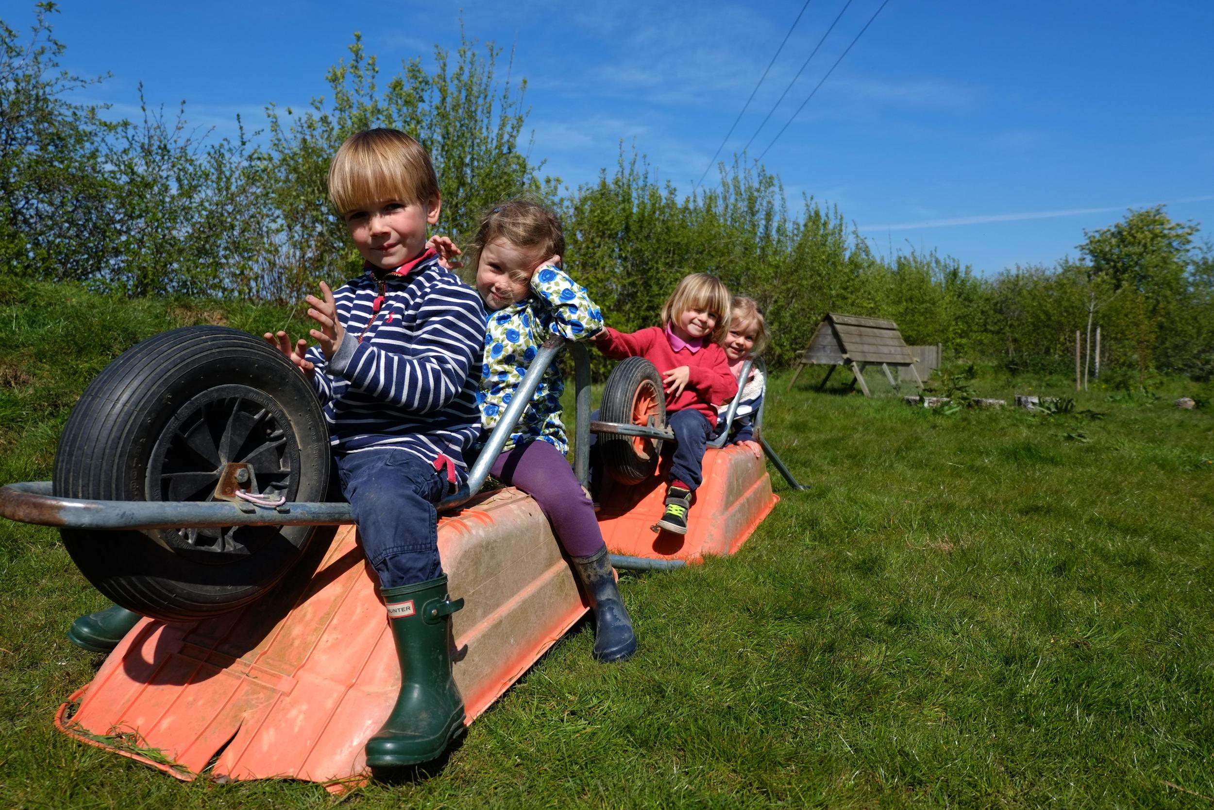 Kids sitting on a pair of wheelbarrows