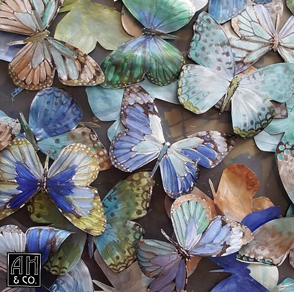 Detail photo of the butterflies being created with custom blended shimmer paint- replicating the true natural iridescence of their wings.