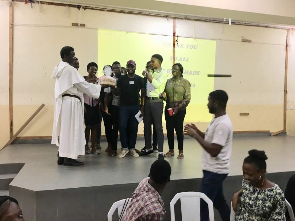 Fr Paul (OP) with some of the students posing with a special cake during Alpha Celebration Mass