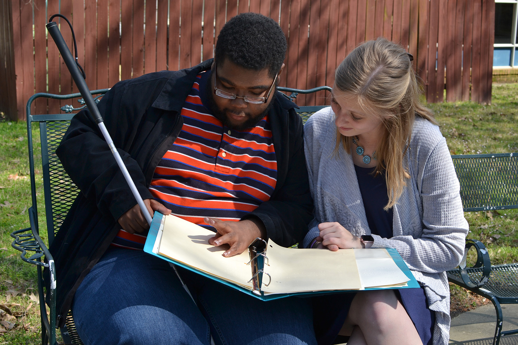 Photo of student and instructor sitting on a bench reading a  Braille book.