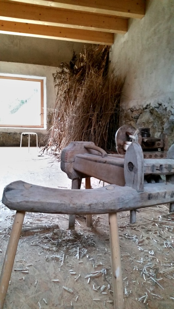 In the corner: Dried hemp stalks. Each stalk must be pressed using the wooden mechanism (pictured in the foreground) to separate the shell from the fiber. Once the shell is discarded, the fibers are combed and can be spun into yarn.
