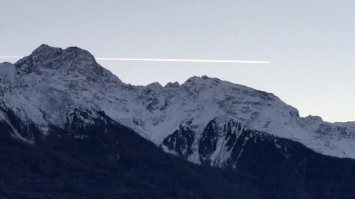 An airplane passes over the glaciers of the Ortler mountains where the Laas marble is mined.