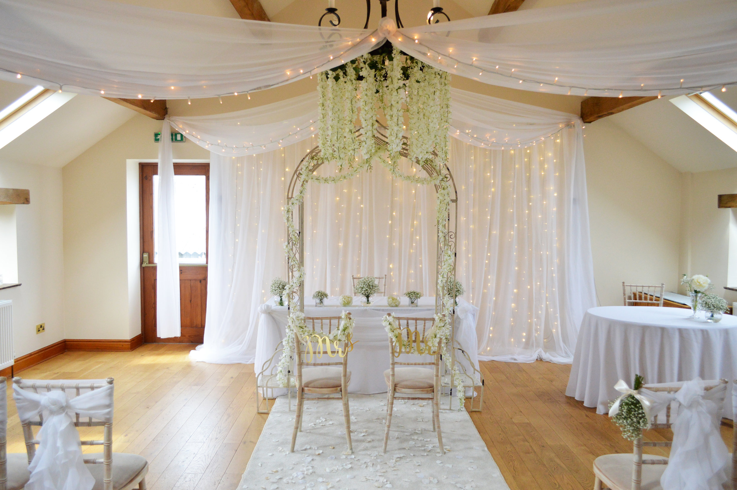 Blossom hanging from chandelier with arch way and fairy light backdrop