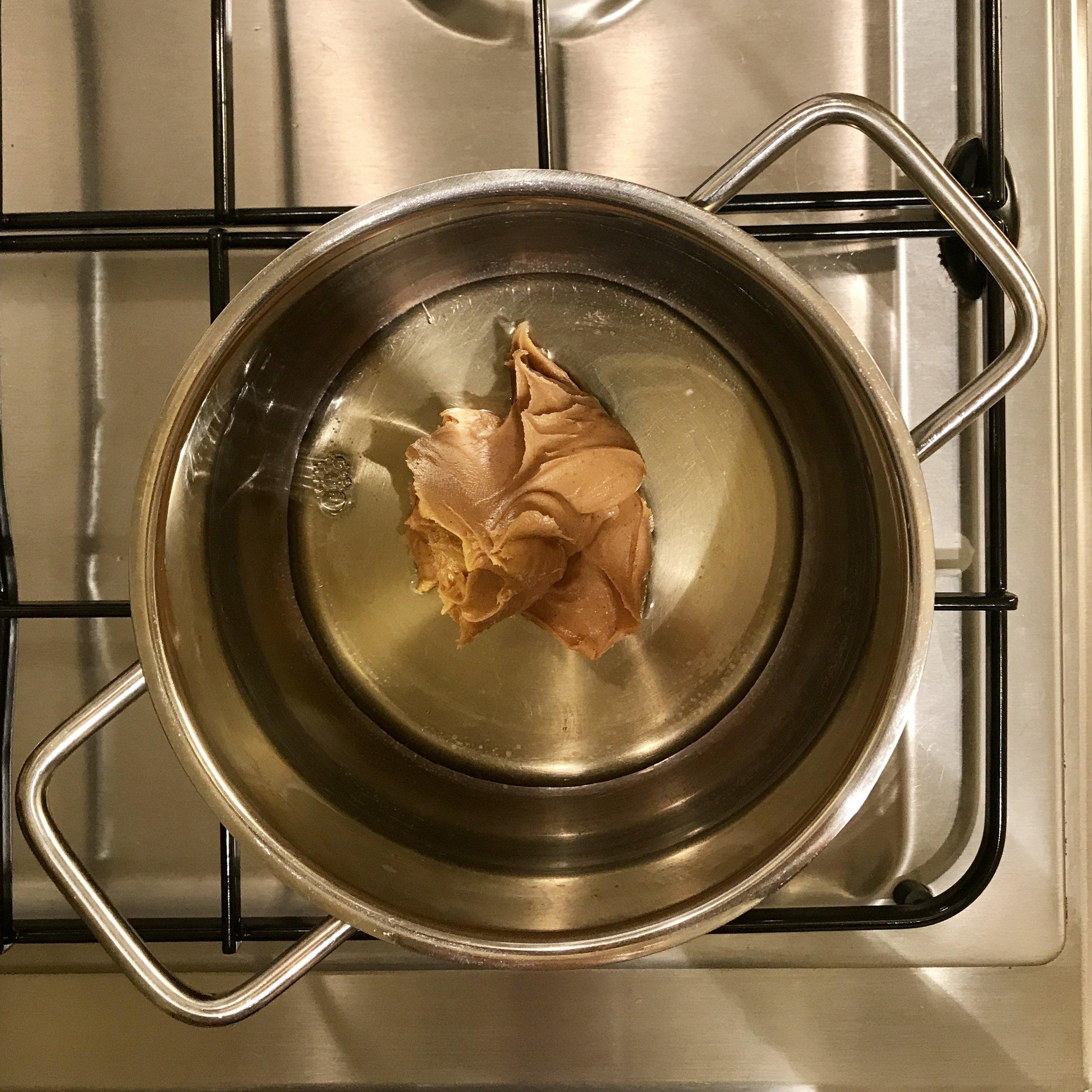 Erdnussbutter und Agavendicksaft auf kleiner Flamme erhitzen und verrühren