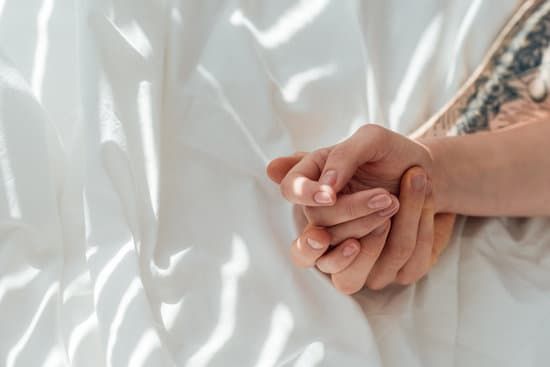 canva-partial-view-of-loving-couple-holding-hands-while-lying-on-white-bed-sheet-MADap1s1-sI.jpg