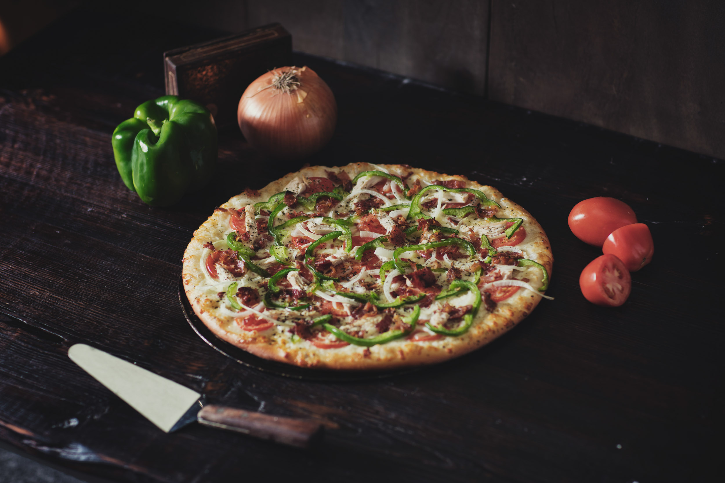 Fresh baked hand tossed pizza with tomato, green pepper, and onion on table