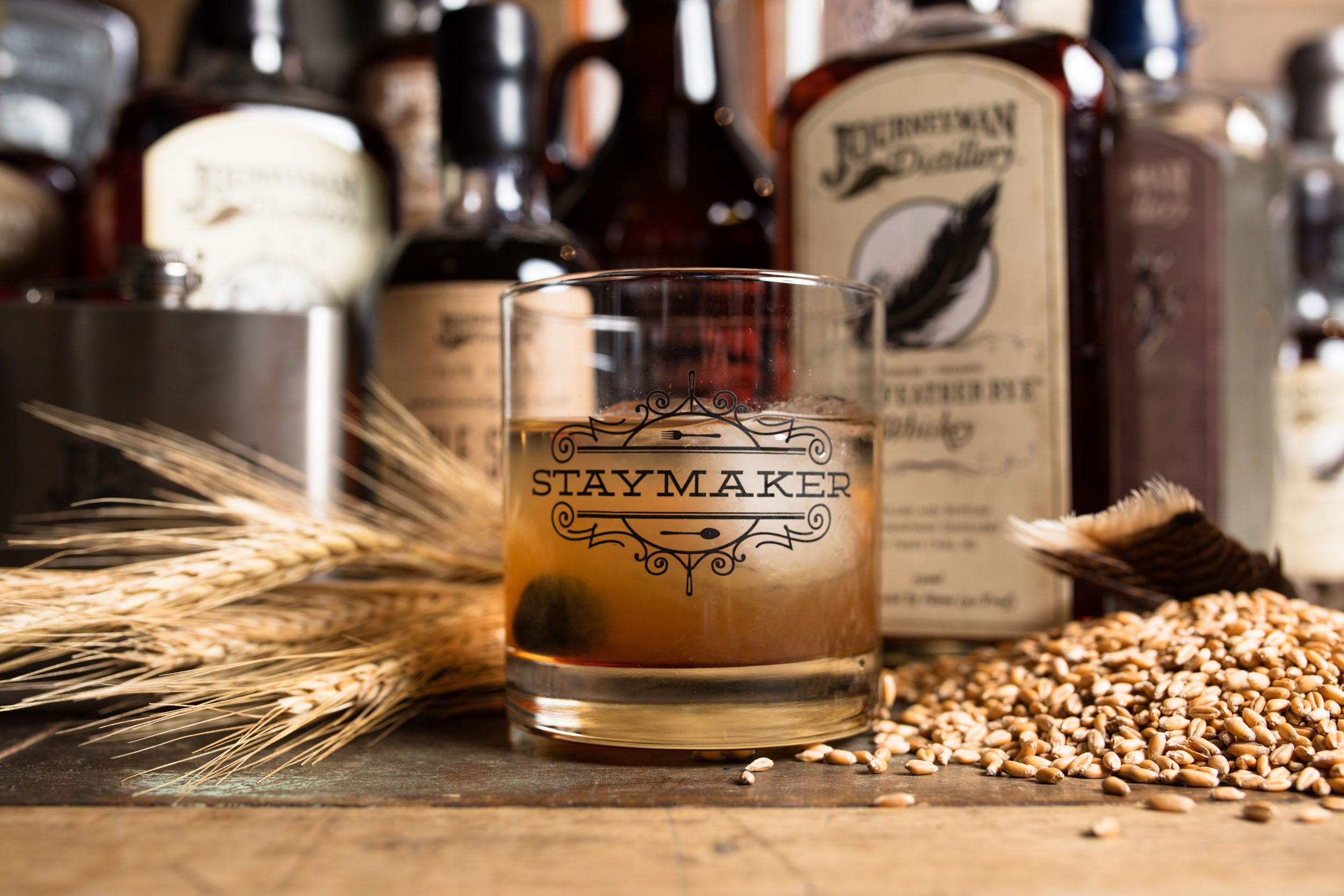 Journeyman Distillery whiskey in a rocks glass with grain on a wood table