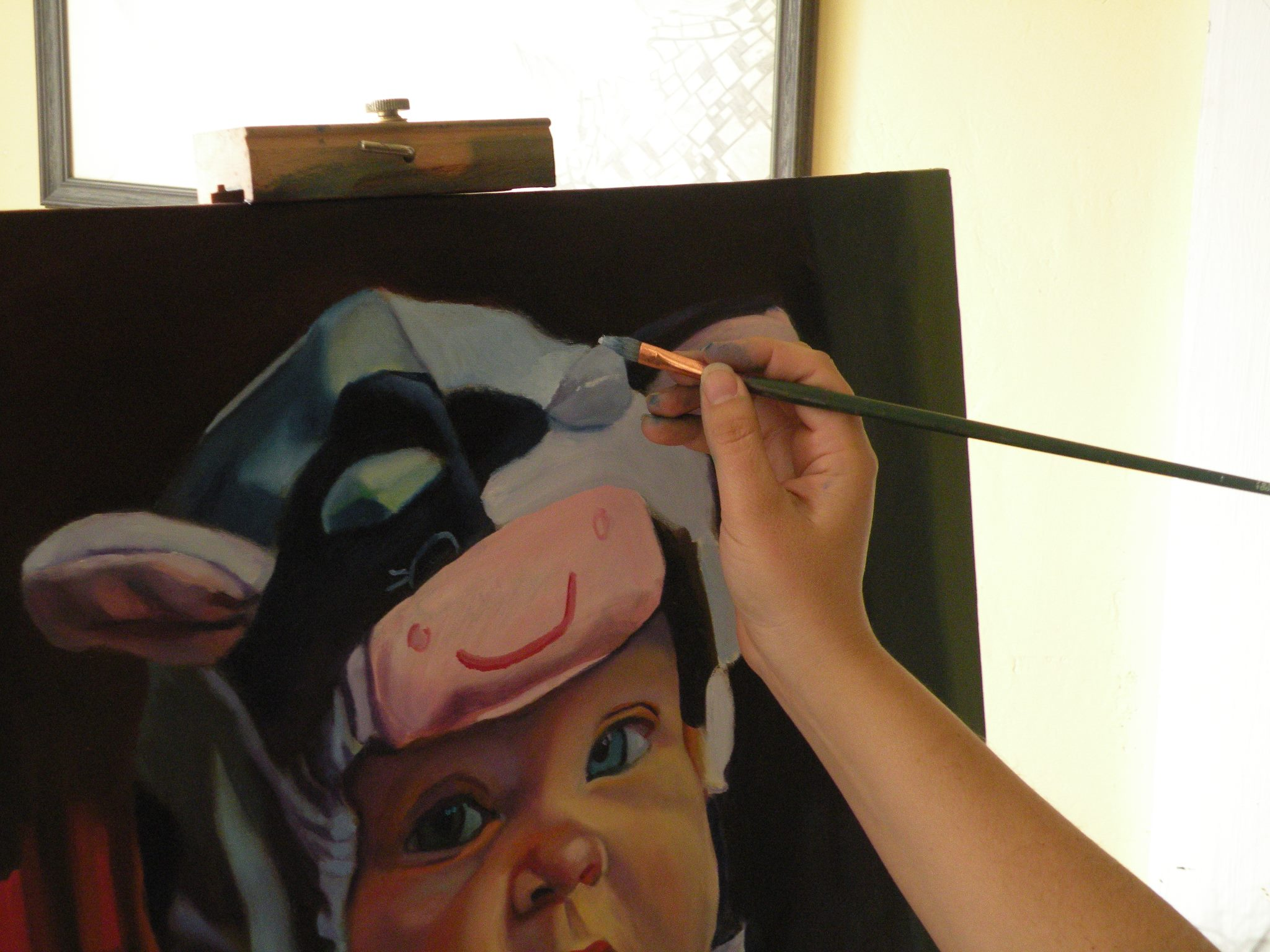 Painting a sweet little girl in a cow costume.