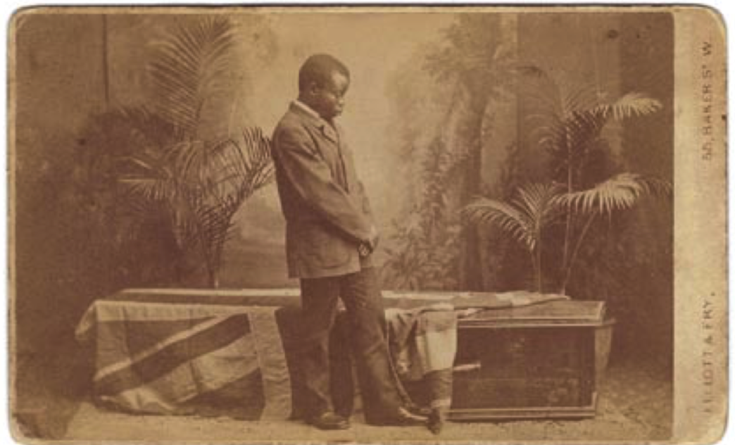 Photograph of Livingstone's coffin, attended by Jacob Wainwright. Carte-de-visite, albumen print, 6.5 x 10.5 cm.  London, Elliott & Fry, 1874.