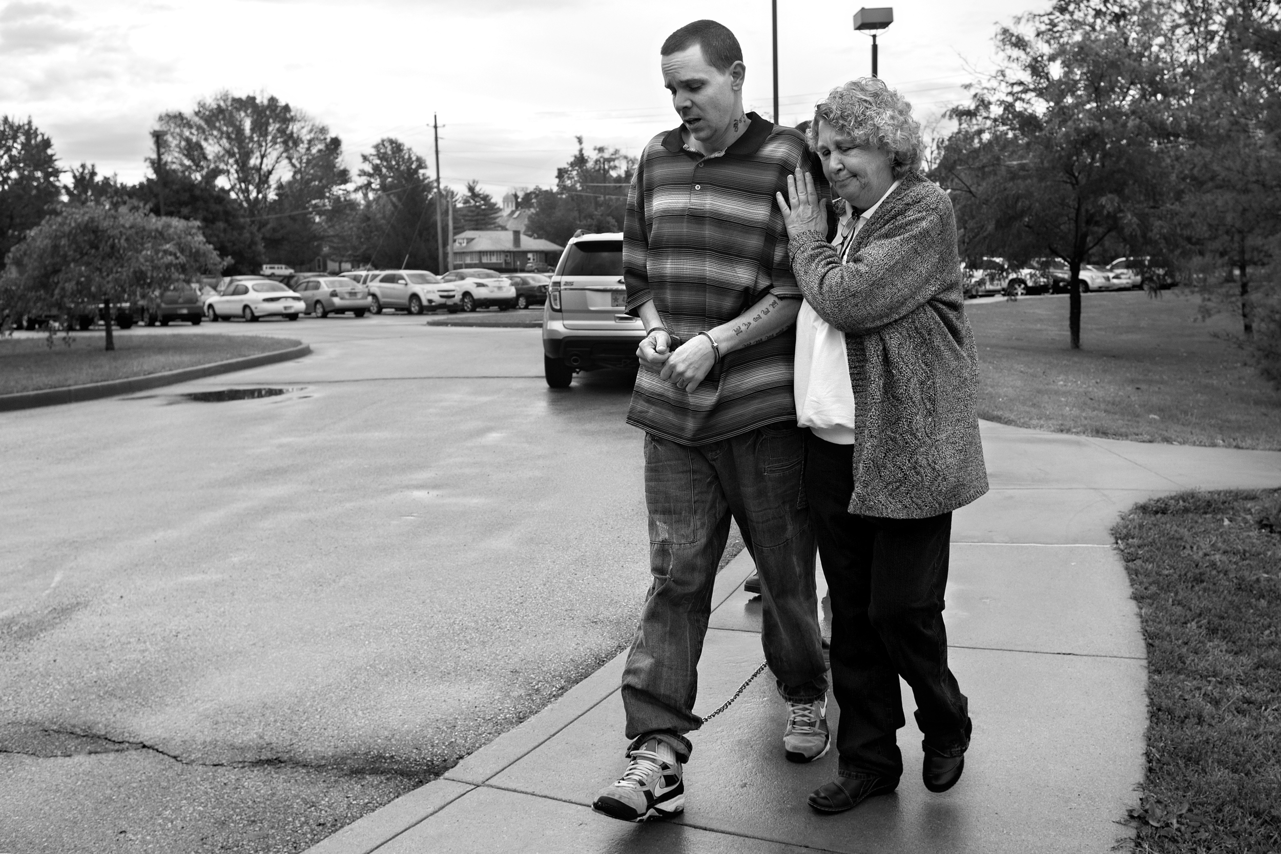 """Following Paul's release from jail, Lynda is relieved as she walks with her handcuffed son who is to be admitted at the Richmond State Hospital. """"I'm safe and he's safe,"""" she said. """"He's not behind bars. He's going to get his proper care and his proper treatment now."""""""
