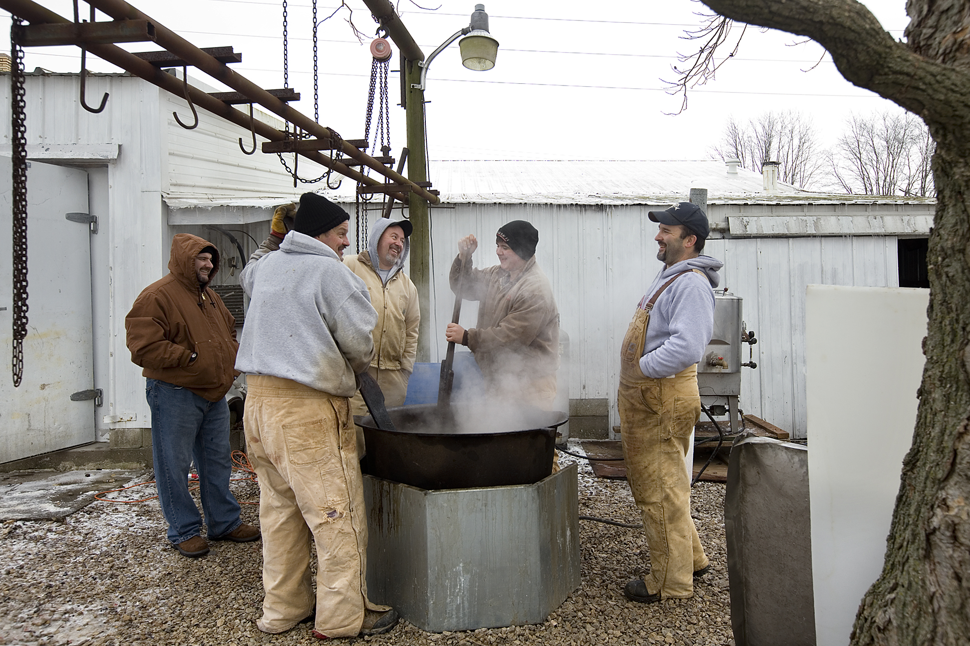 Rendering the lard was one of the last tasks the Schwenk family finished before the final cleanup began. The rendering process requires the lard to be constantly stirred, so Mark Kordes of Jasper, clockwise from front left around the kettle, Roy Main of Ireland, Nicholas Hoffman of Birdseye, 16, and Nathan Verkamp of Jasper took turns stirring the lard. Josh Dahmer of Evansville, back left, watched and helped stir as well.