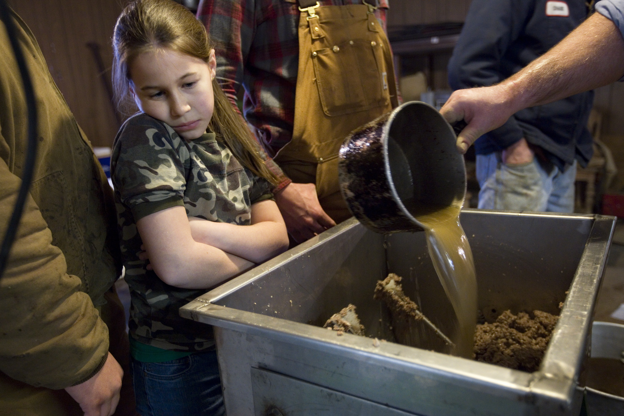Hannah Schwenk of Jasper, 9, watched as the head cheese was mixed. While some of the family members don't like the head cheese, the several members that do say it's best served on a cracker with spicy mustard.