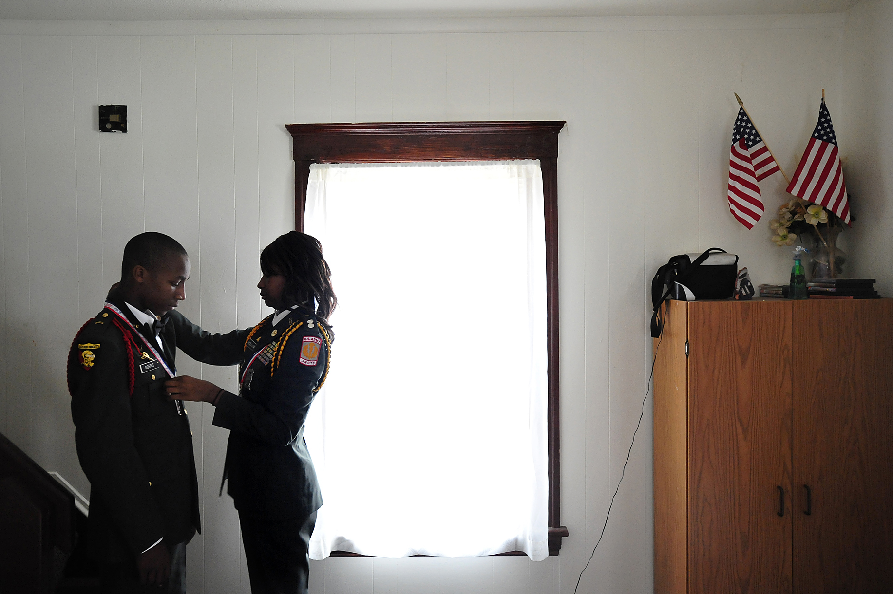 First Lt. Leticia Holloway, right, situated a medal on her brother, Cpl. Dyron Norris, as they prepared for the Army Junior ROTC annual military ball.