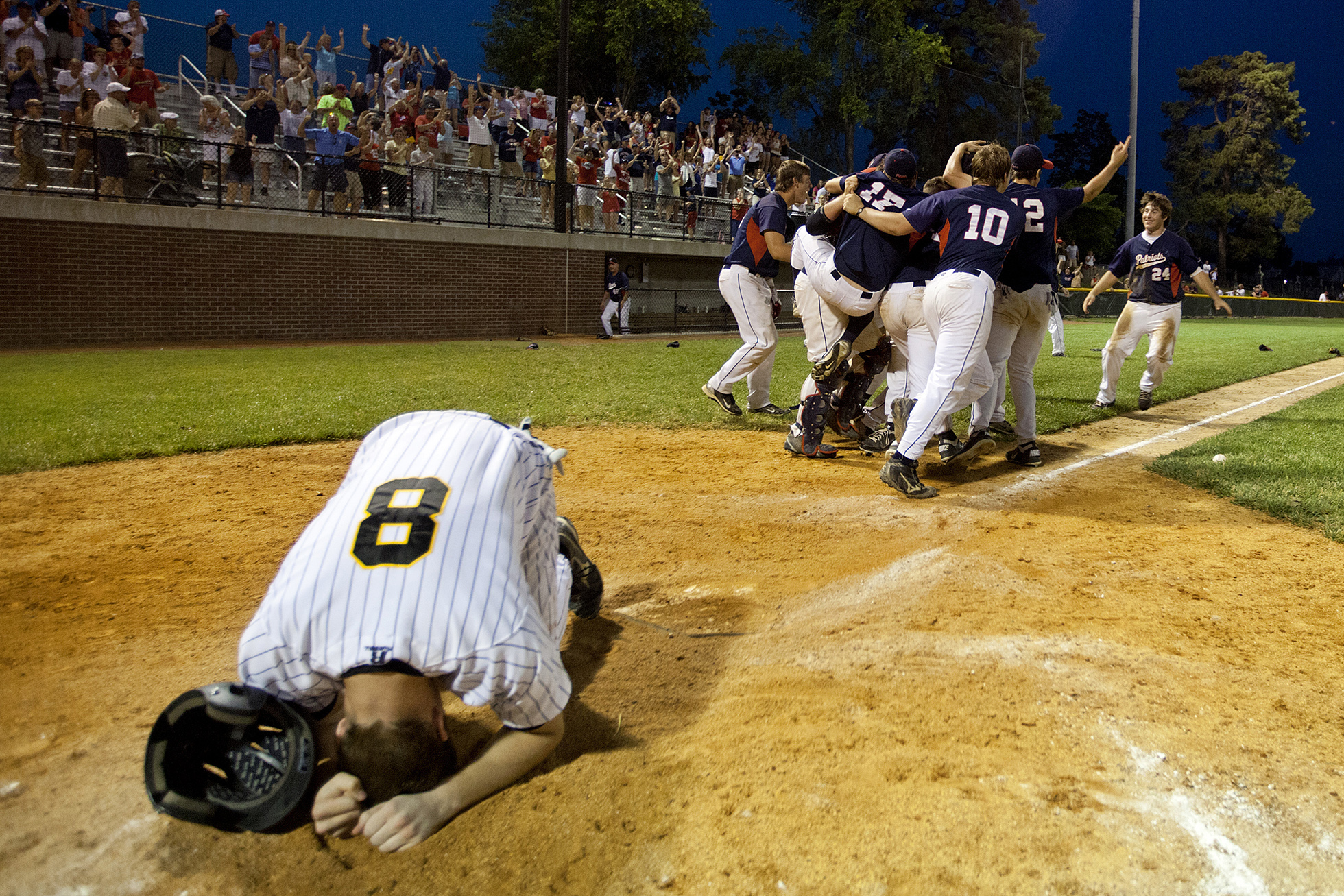 Jasper's Dane Giesler lumped to the ground after being thrown out at home plate for the final out of the Class 3A sectional championship at Ruxer Field in Jasper. That was the cue to celebrate for Heritage Hills, which hung on to win 4-3 and claim its first sectional title since 1997.