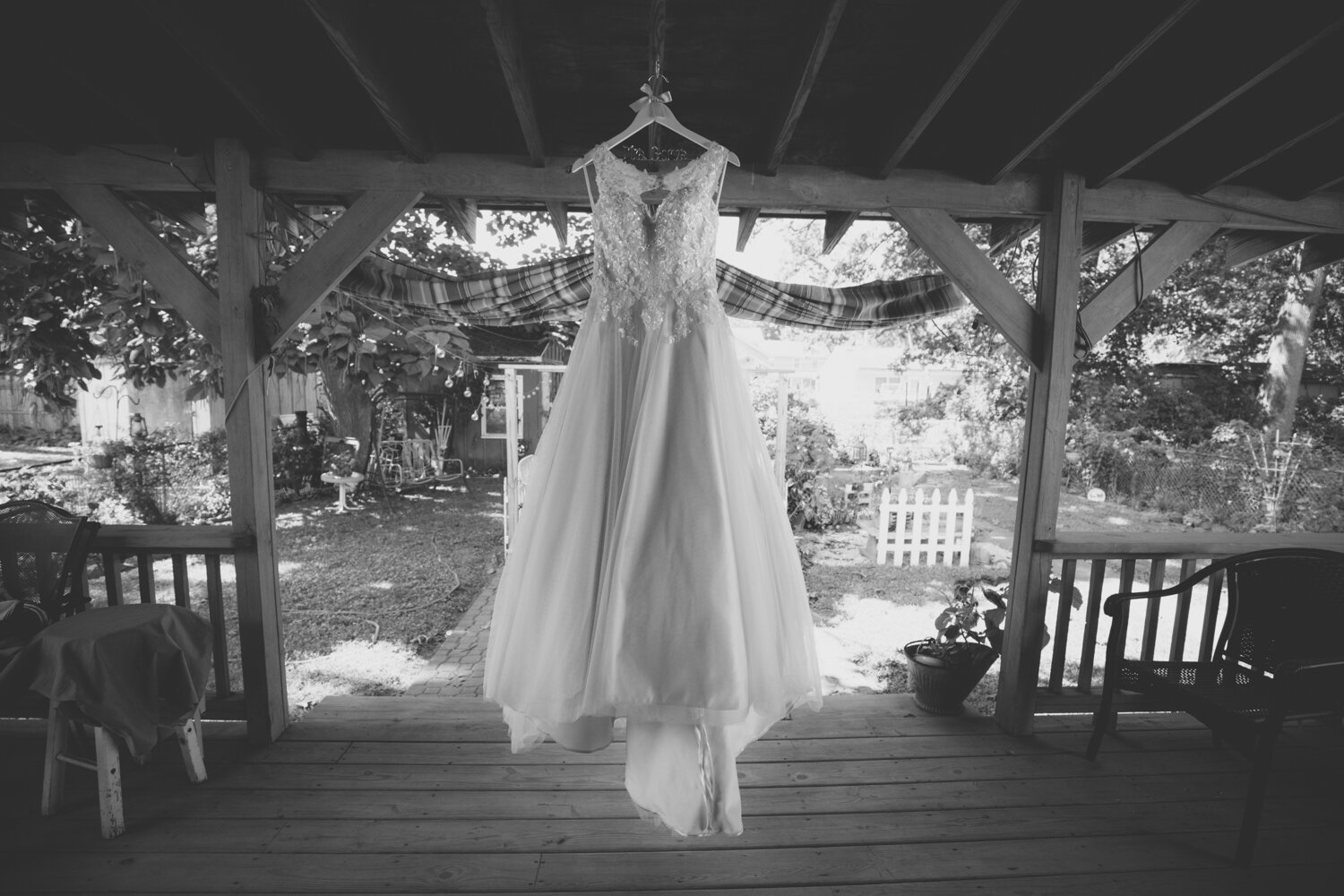 Black and white image of a wedding dress on a porch