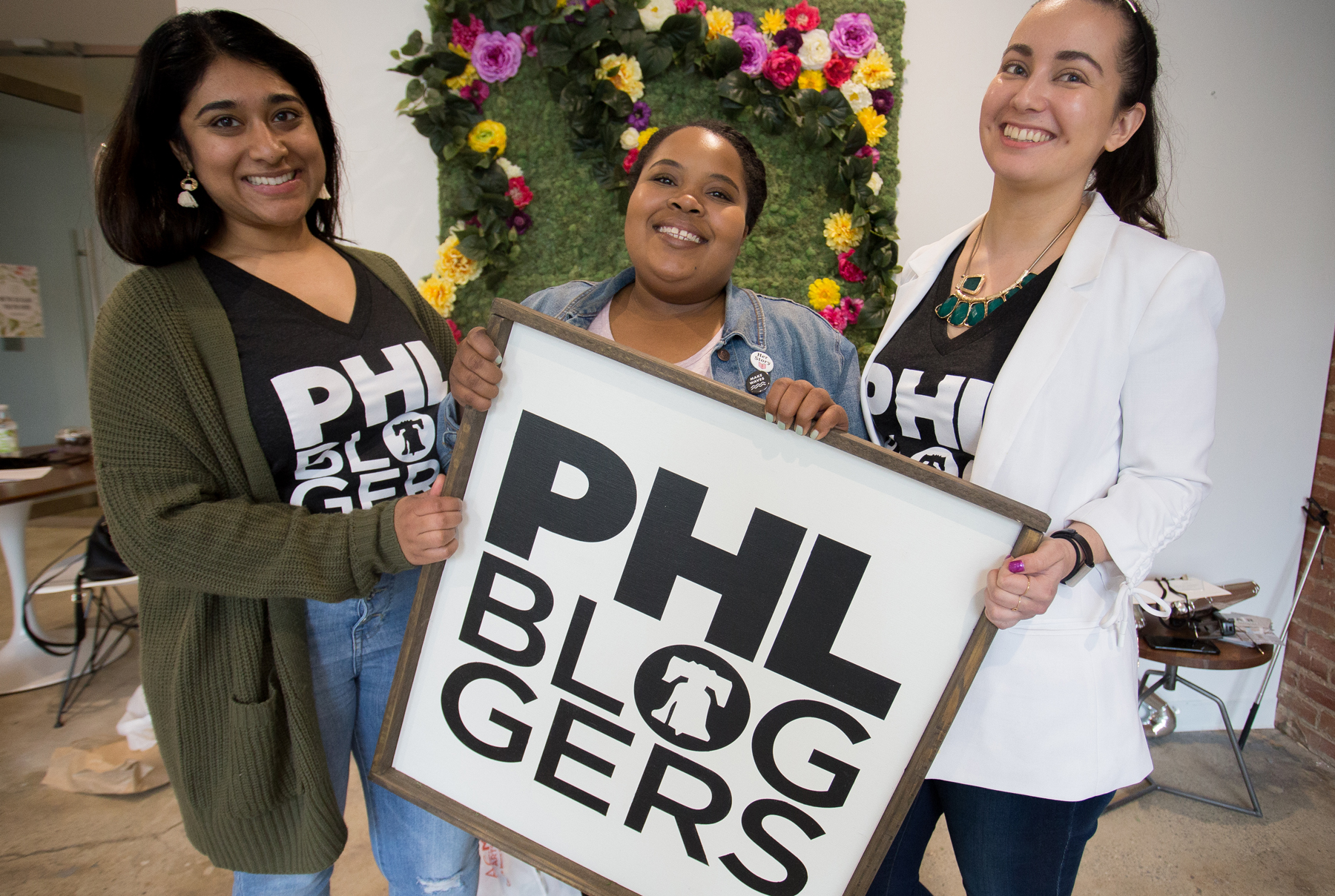 The Blog Connect team members Priyanka (left) and Sarah (right) posing with speaker and workshop lead Amber Burns (middle) showing off our new PHLbloggers sign made by A.R. Workshop in Chestnut Hill in front of our beautiful flower wall made by A.C.Moore. || Photo by  Tim Becker Photography