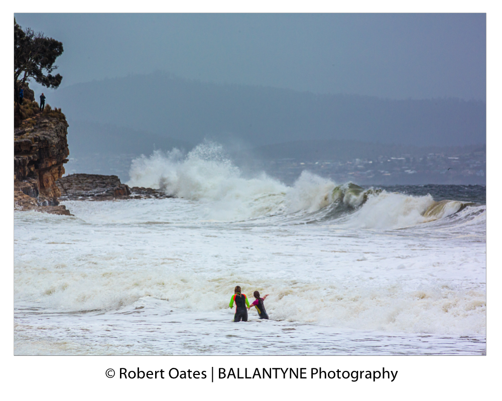 Children body surf in the shallows