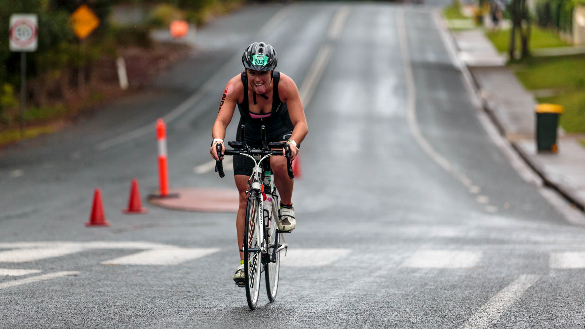 Personifying the spirit of the day, Demi Greentree, an Ironman 70.3 competitor, in the pouring rain with a 10km cycle and half marathon still to run, produced this great smile.