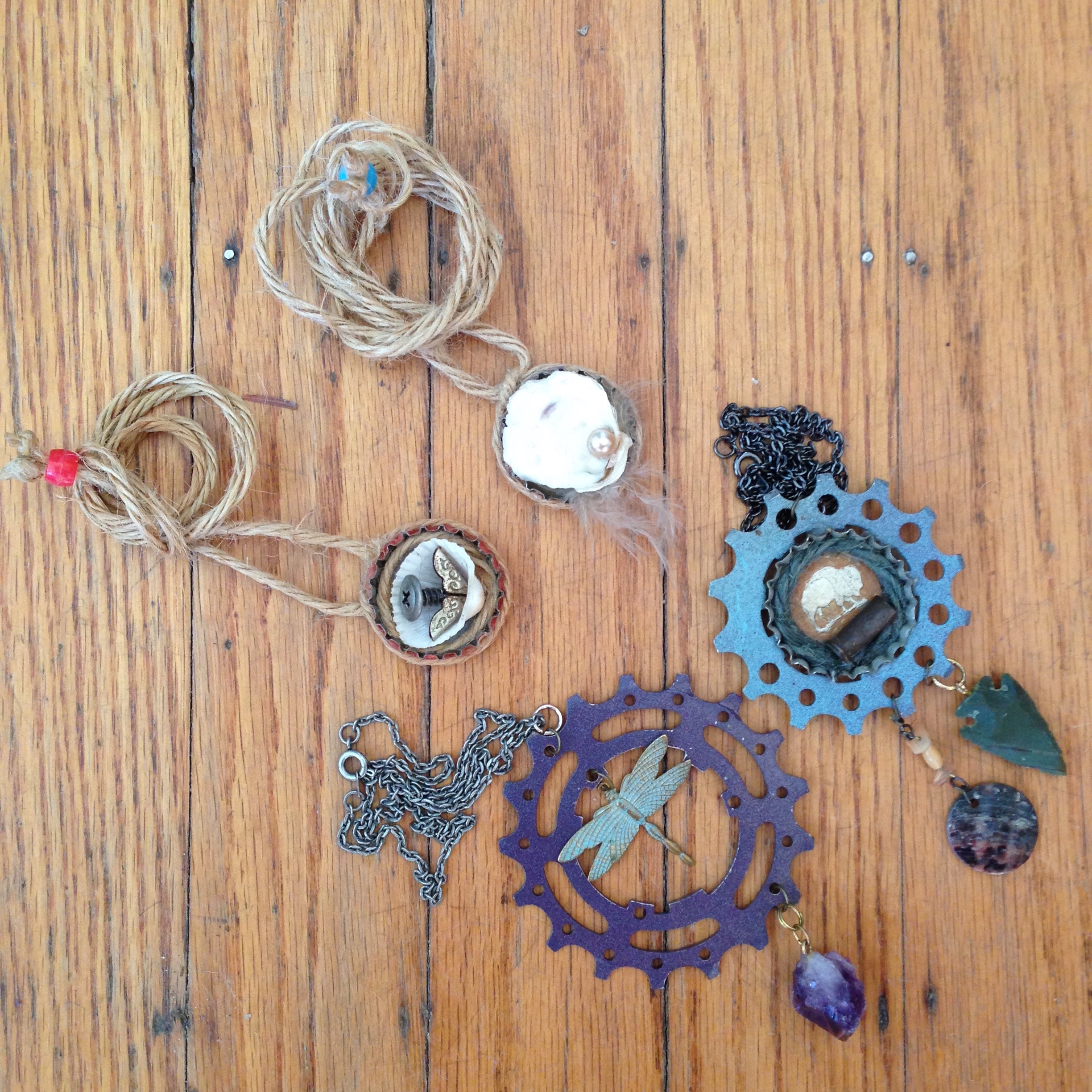 Adjustable bottle cap necklaces and bicycle gears on chains with gemstones.