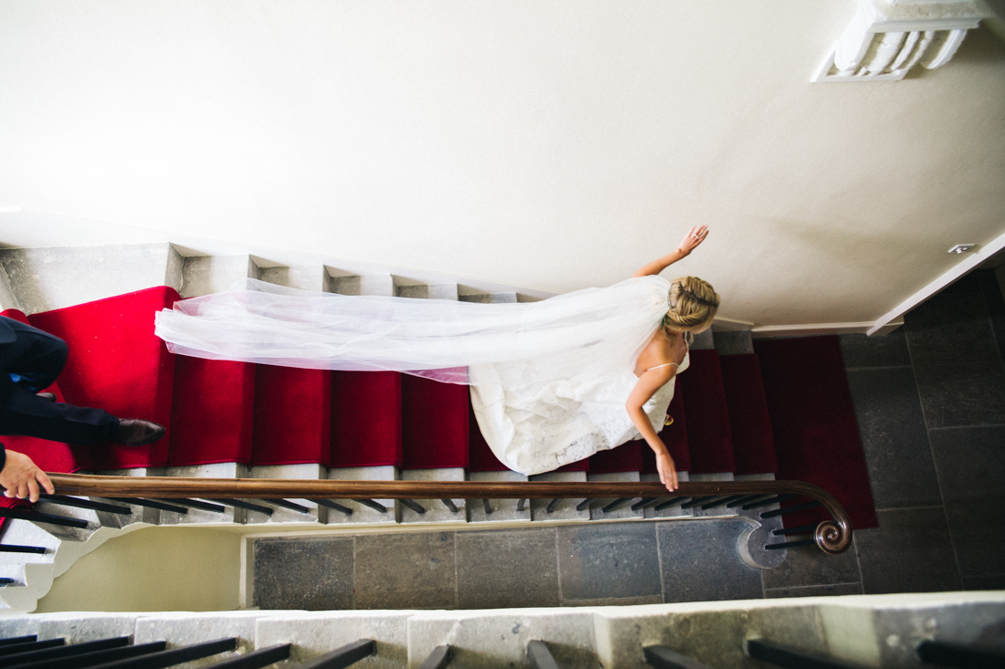 a bride walks down a staircase with a red runner. marquee wedding in stirling, scotland. stop motion wedding films videos uk