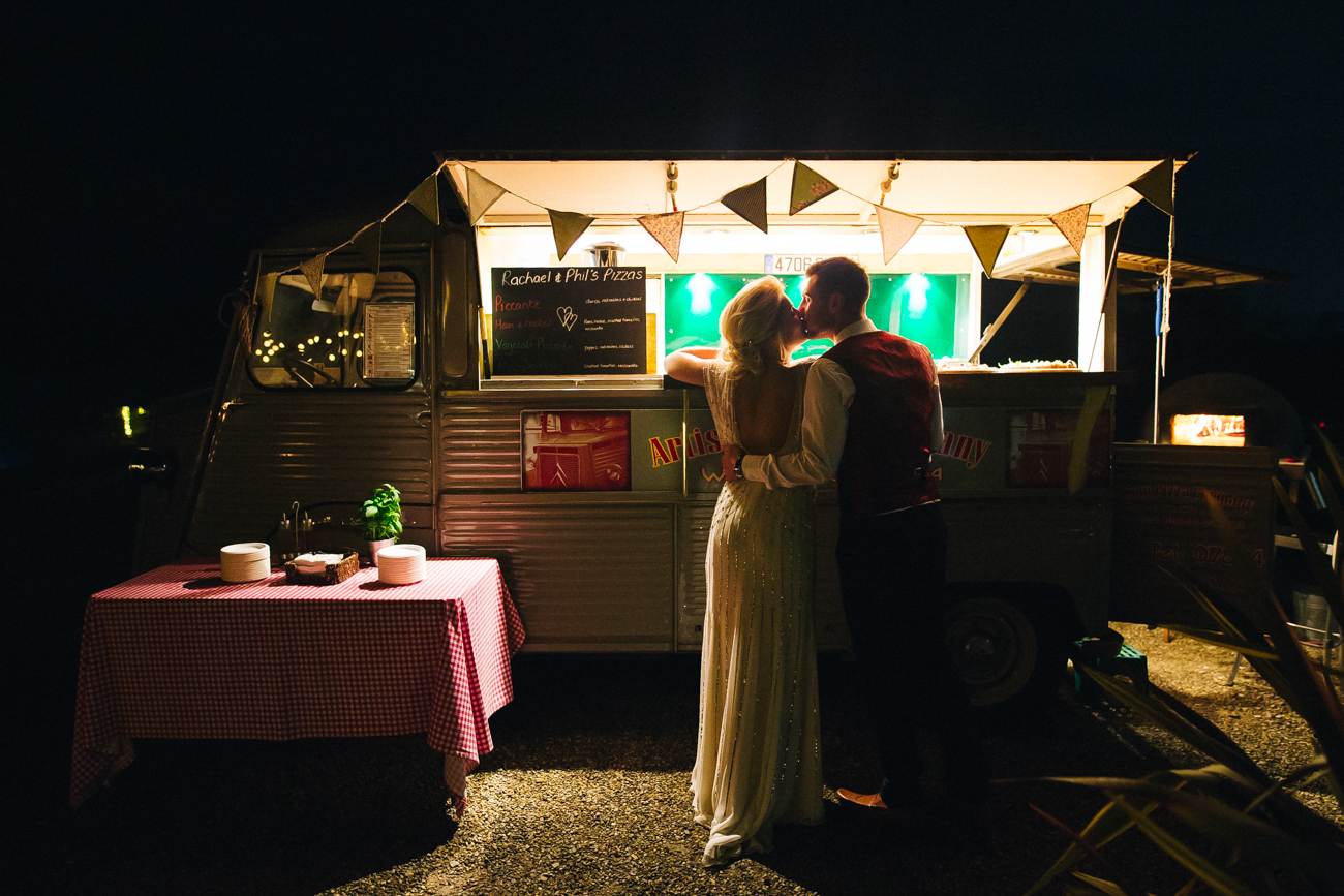a bride and groom kiss outside a pizza van. creative wedding photography north yorkshire teesside north east + stop motion wedding films uk