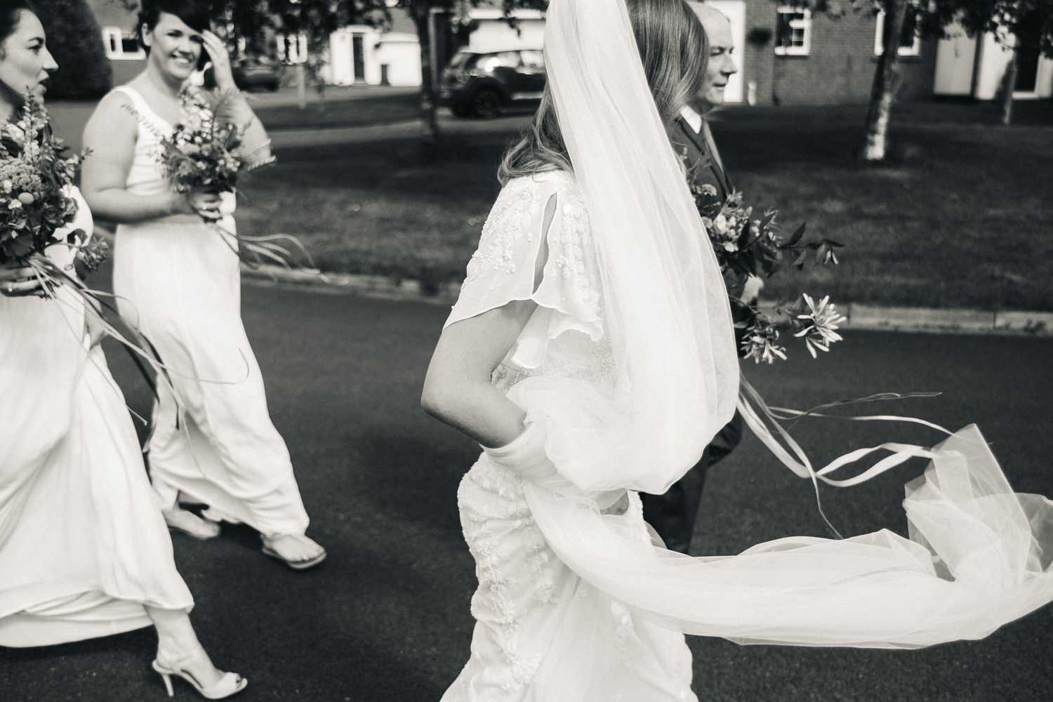a cropped and moving shot of a bride and her bridesmaids walking to the church. Her veil blows in the breeze. wedding at the crab and lobster in north yorkshire. stop motion wedding films videos uk