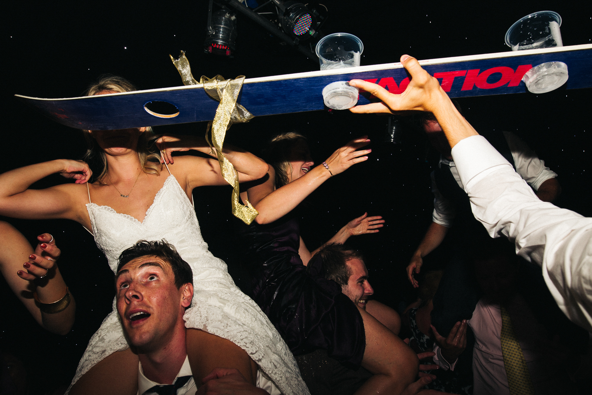 a busy dancefloor shot with a bride on the shoulders of a guest. marquee wedding in stirling in scotland. stop motion wedding films videos uk