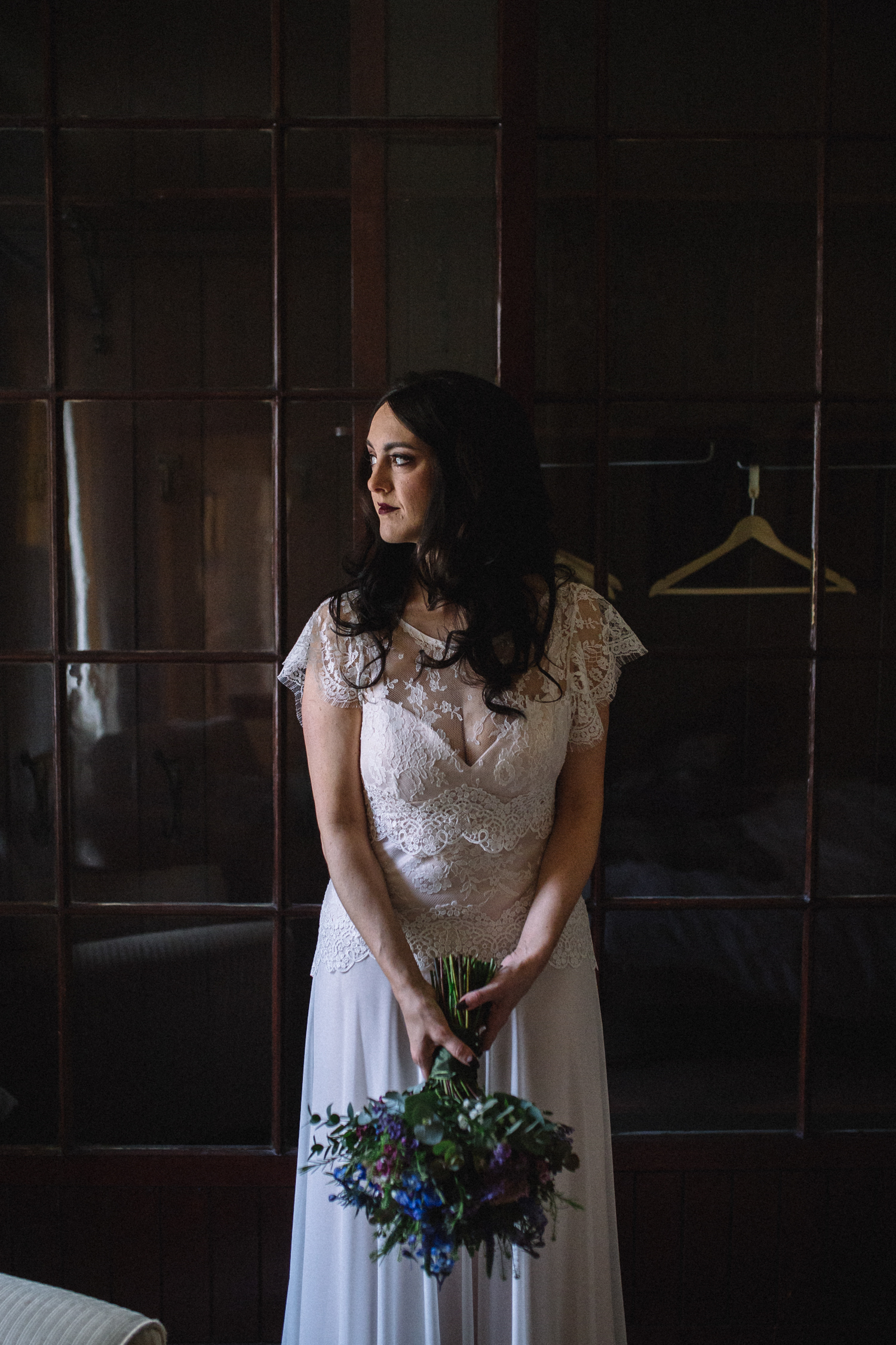 a bride stands in her wedding dress holding her bouquet looking to the side into the light. eshott hall northumberland wedding. stop motion wedding films videos uk