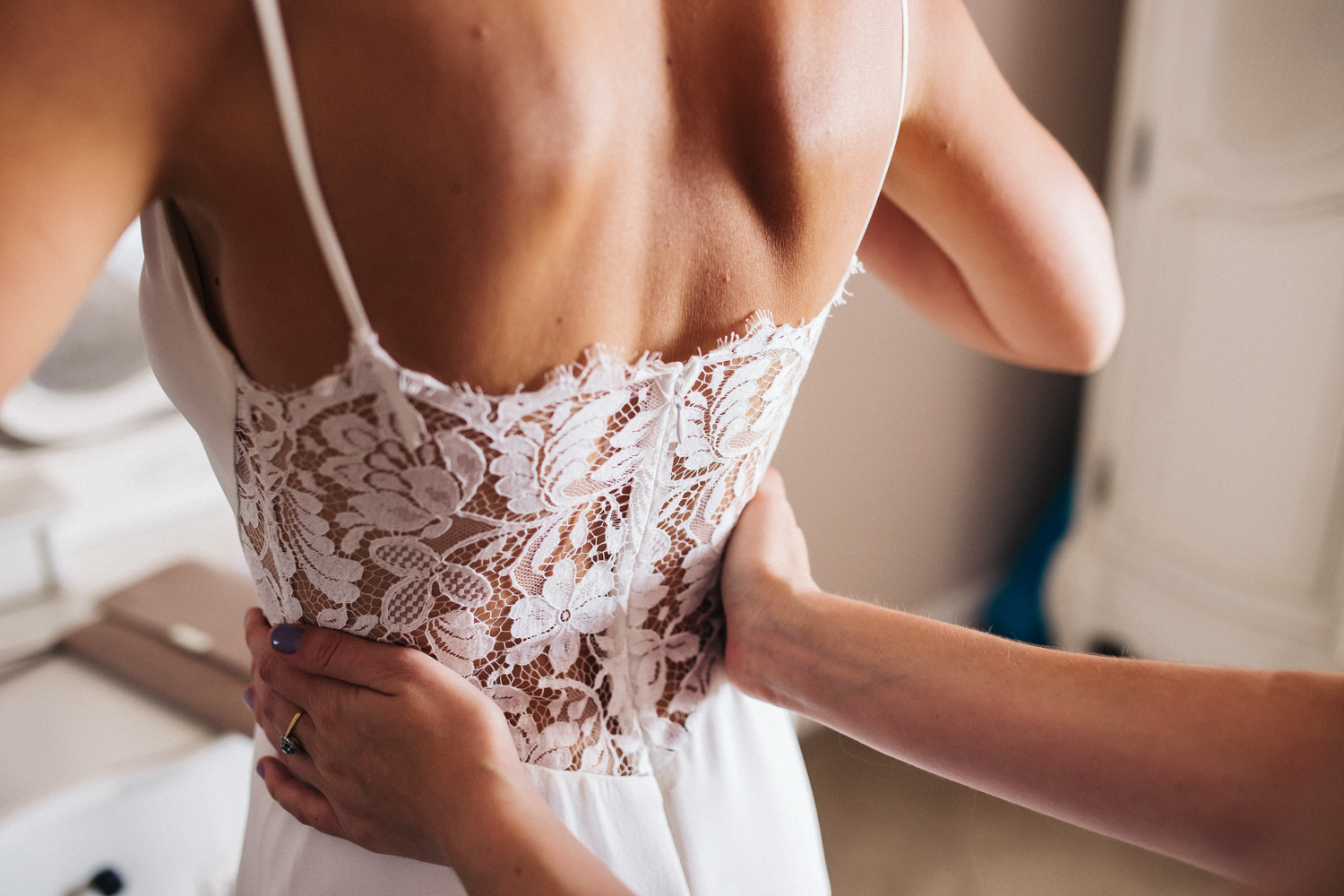 a close shot of the back of a bride, details of her lace wedding dress. sandhole oak barn cheshire wedding photographer. stop motion wedding films videos uk