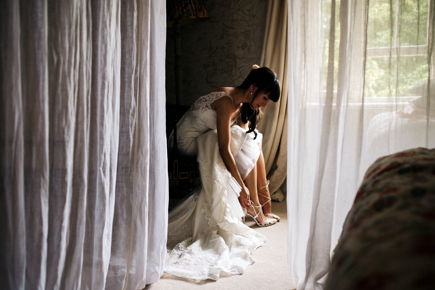 woman sitting in a wedding dress, putting her shoes on. wedding at dewsall court hereford. stop motion wedding films videos uk