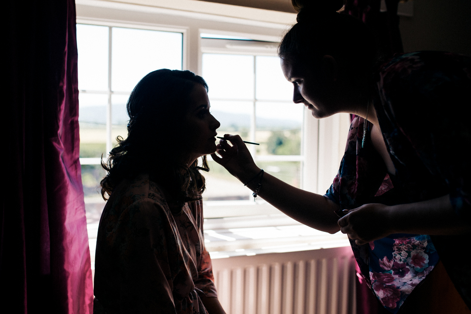 a bride is silhouetted as her make up is applied. village hall wedding venue north yorkshire northallerton. stop motion wedding films videos uk