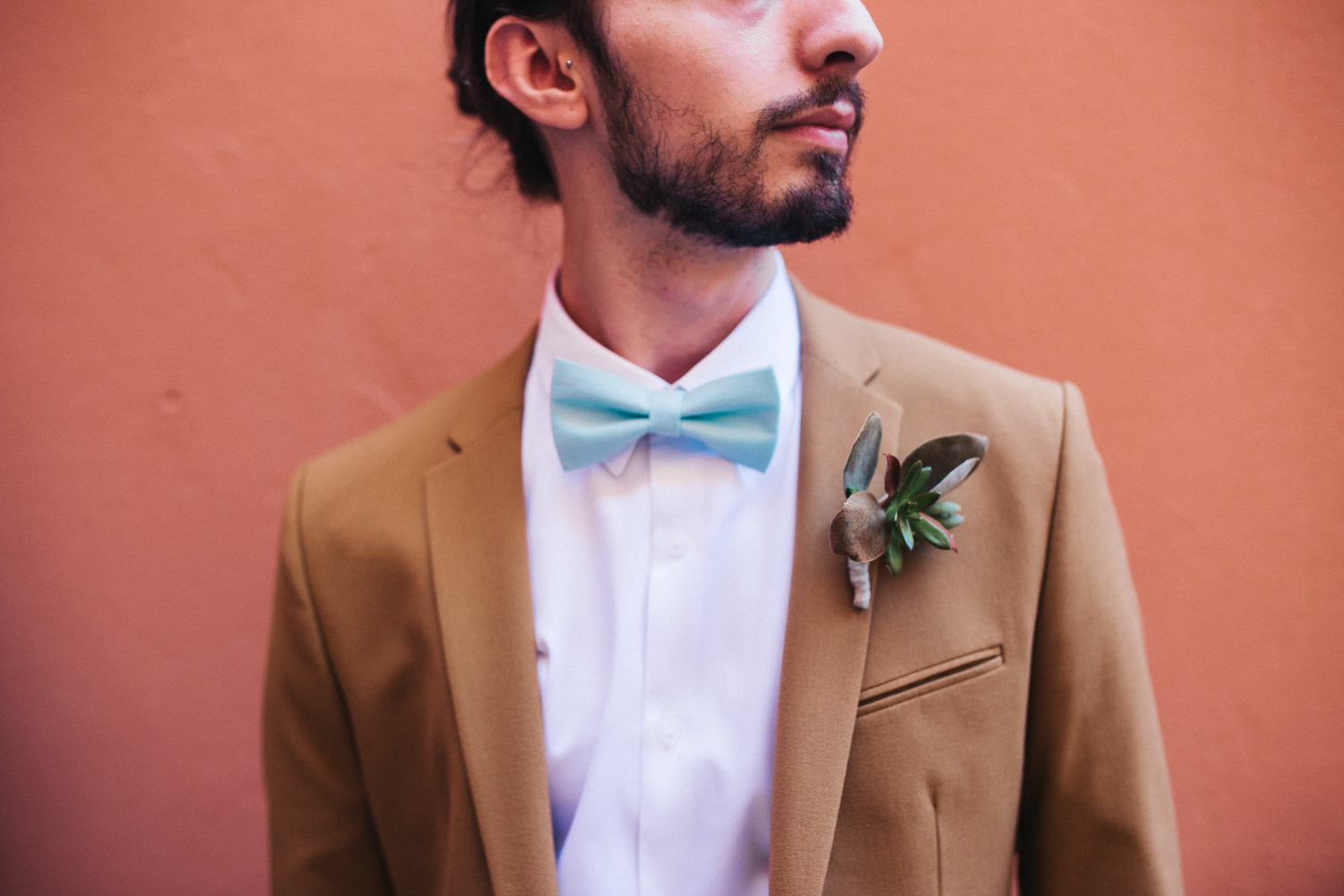 cropped image of a groom in a brown suit looking to the side. He's wearing a mint green bow tie and succulent corsage. destination wedding at hotel monte rosa italy. stop motion wedding films uk