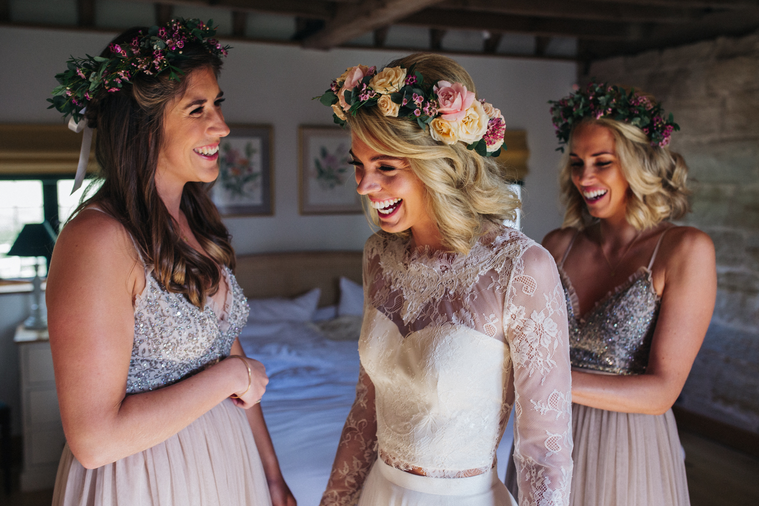 a bride laughs with her two bridesmaids as they do her dress up. hendall manor barn wedding near brighton. stop motion wedding films videos uk