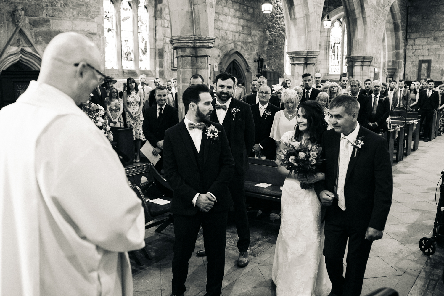 a groom looks happy and surprised at the sight of his bride at the bottom of the aisle. village hall wedding north yorkshire. stop motion wedding films videos uk