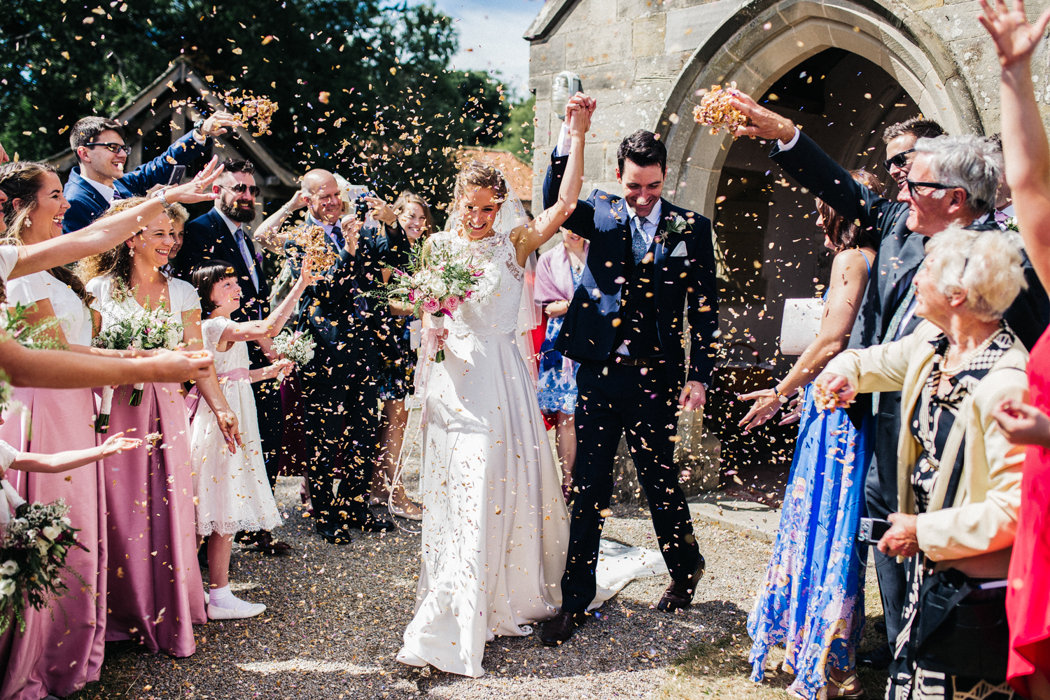 a bride and groom cheer walking through confetti and lines of guests. aldby park marquee wedding york. stop motion wedding films videos uk