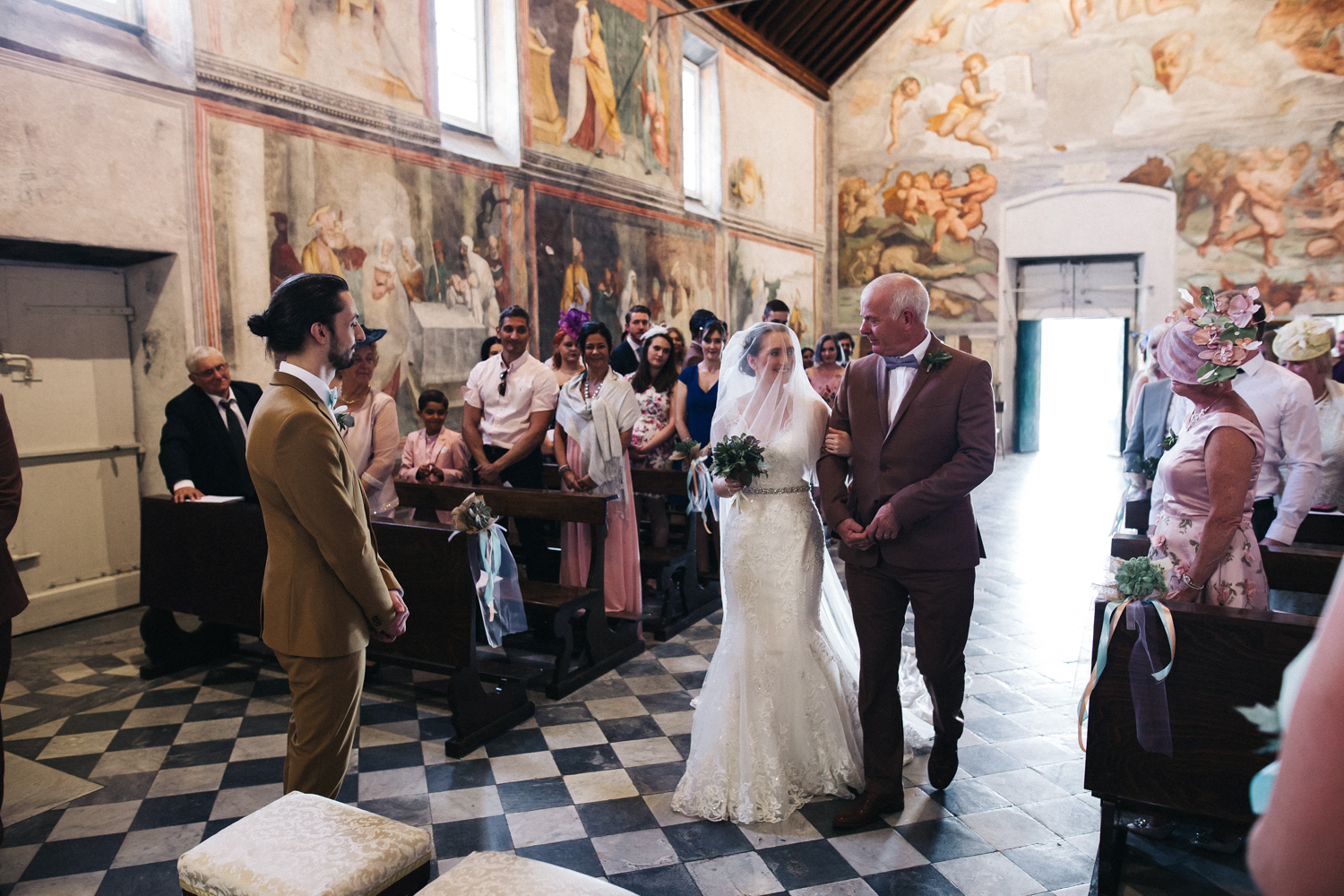 a bride and groom meet at the bottom of the aisle. destination wedding photography italy pisa florence. stop motion wedding films videos uk