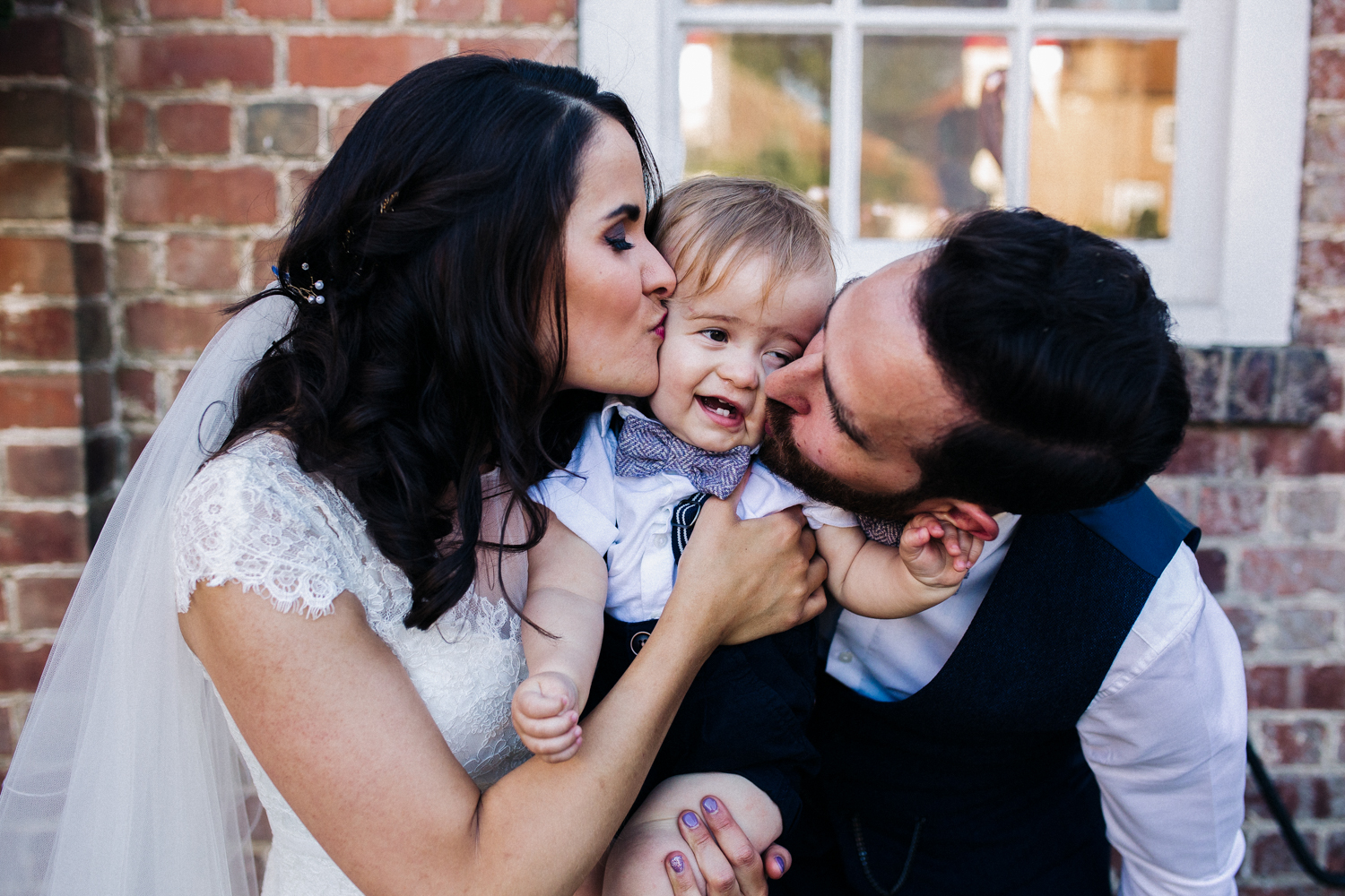 a bride and groom kiss their baby son from both sides as they hold him